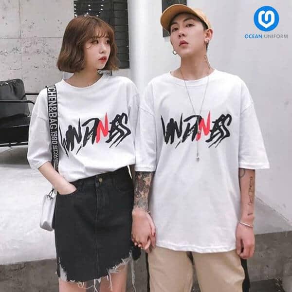 Mẫu áo cặp đôi màu trắng cổ tròn đơn giản với điểm nhấn là dòng chữ in màu đỏ đen sắc nét
